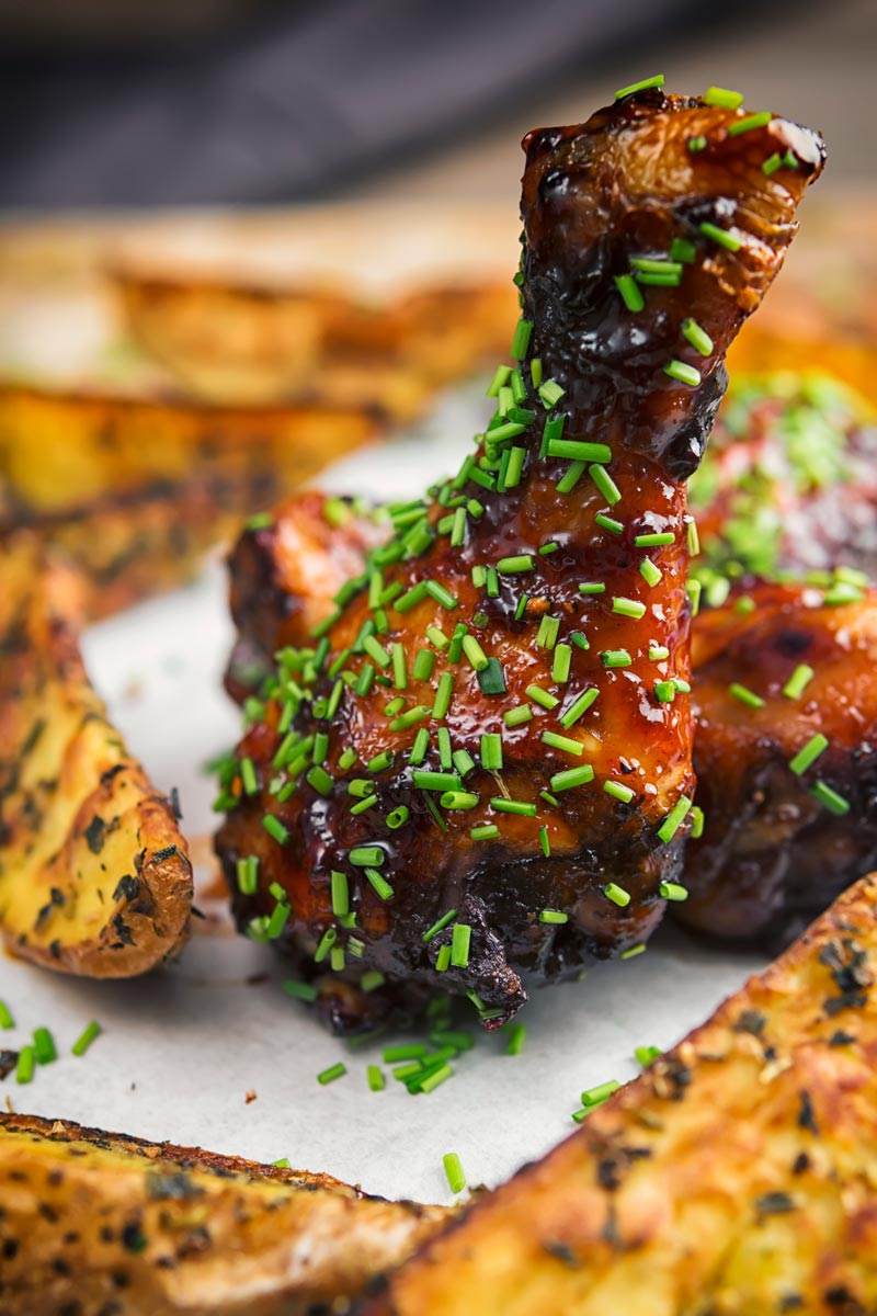 Portrait image of a sticky chicken drumsticks with snipped chives and potato wedges