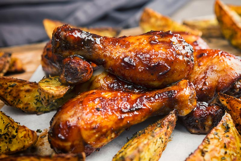 Landscape image of a sticky chicken drumsticks served with potato wedges