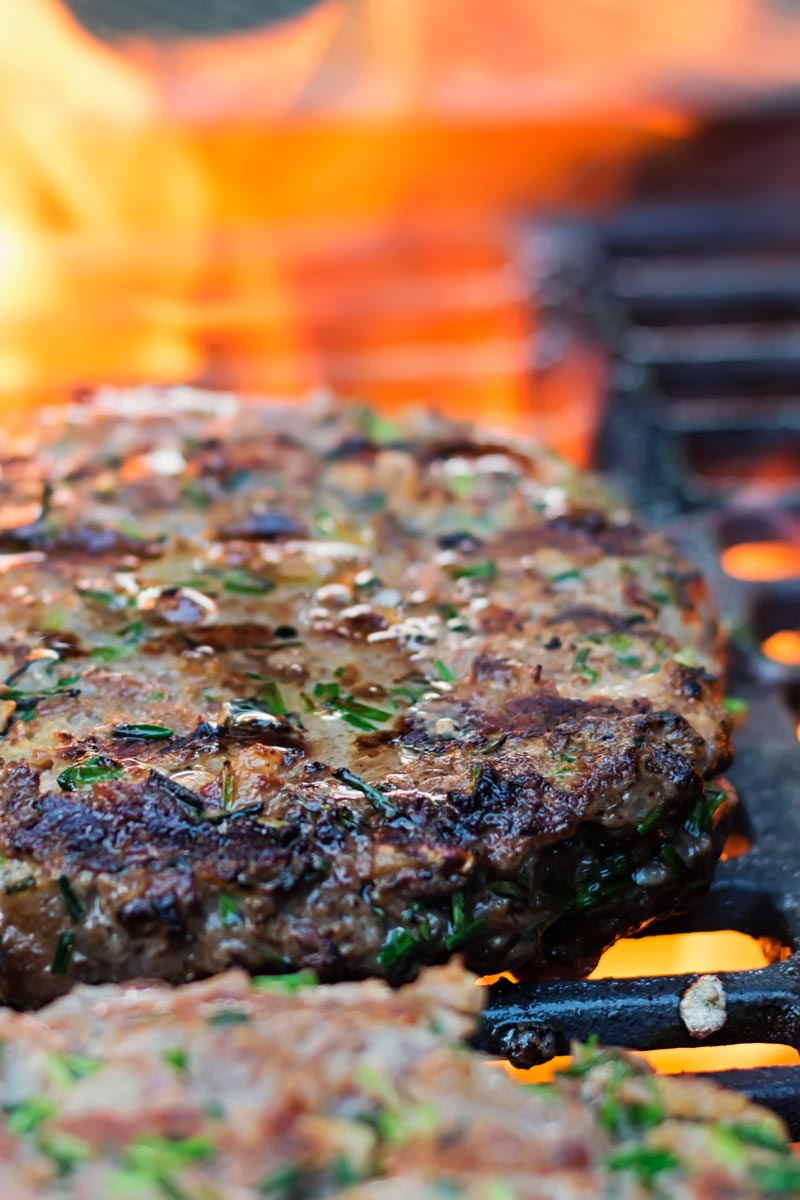Portrait image of venison burgers cooking on a BBQ with a flame