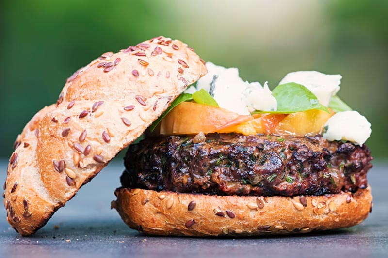 Landscape image of a venison burger with the top removed showing the peach, blue cheese and basil garnish