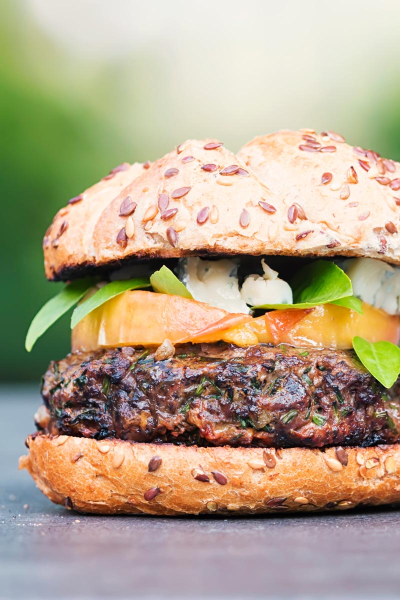 Portrait image of a venison burger with a peach, blue cheese and basil garnish