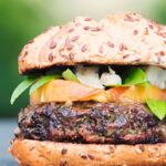 Portrait image of a venison burger with a peach, blue cheese and basil garnish with text