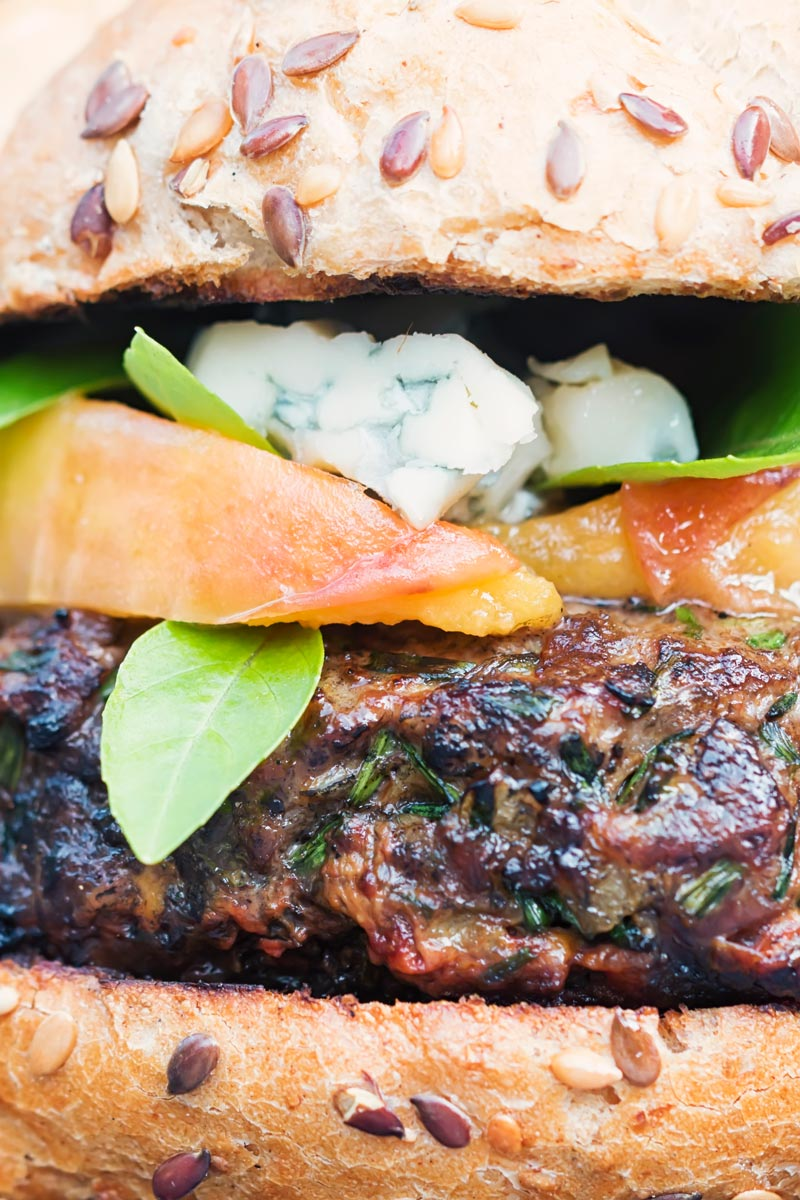Portrait close up image of a venison burger with a peach, blue cheese and basil garnish