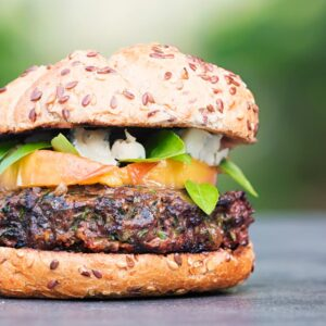 Square image of a venison burger with a peach, blue cheese and basil garnish