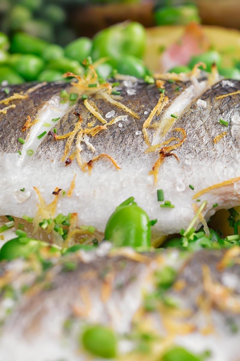 Portrait close up image of baked sea bass fillets slashed and scattered with lemon zest