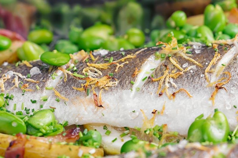 Landscape close up image of baked sea bass fillets slashed and scattered with lemon zest