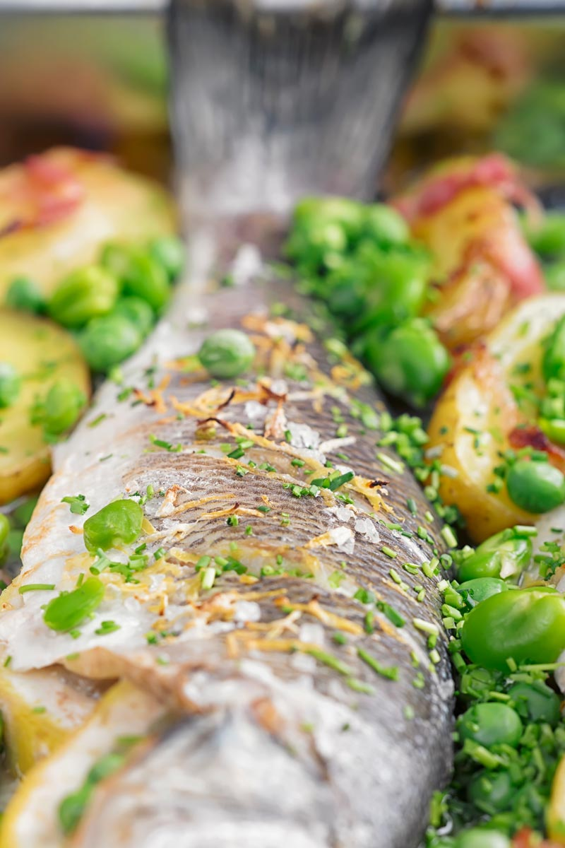 Portrait close up image of whole baked sea bass in a tray with potatoes peas and broad beans