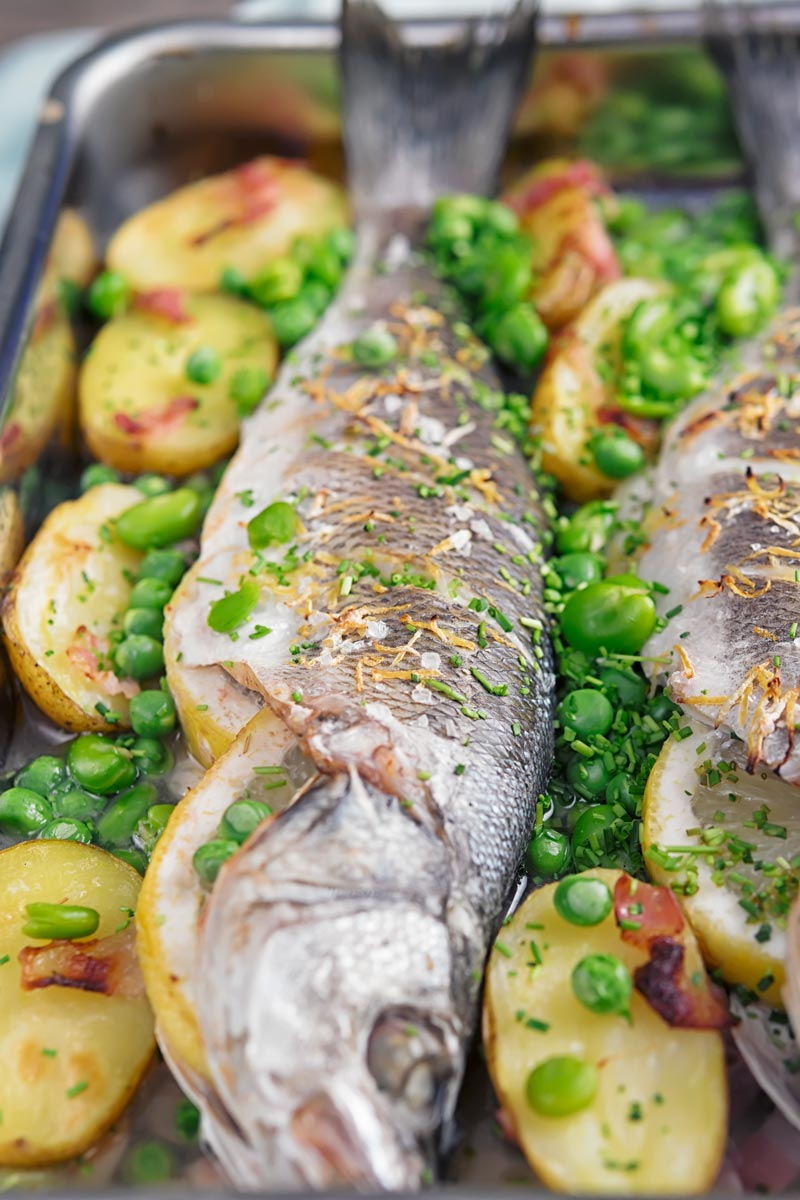 Portrait image of whole baked sea bass in a tray with potatoes peas and broad beans