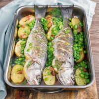 Whole Baked Sea Bass Tray Bake with Potatoes, Broad Beans and Peas.