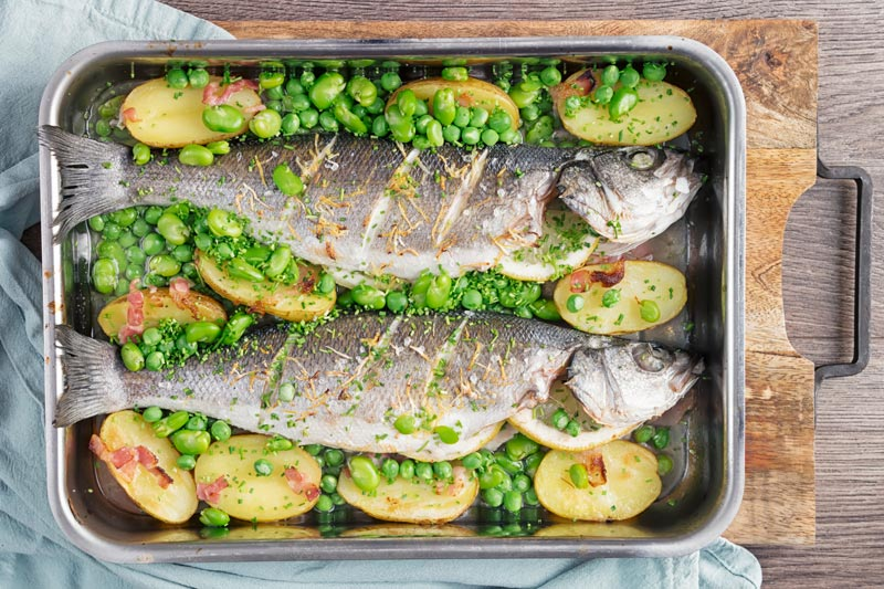Landscape overhead image of two whole baked sea bass in a tray with potatoes peas and broad beans