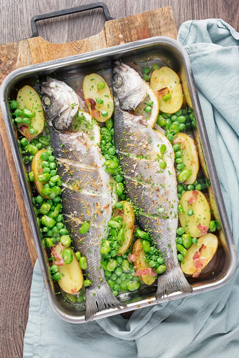 Portrait overhead image of two whole baked sea bass in a tray with potatoes peas and broad beans