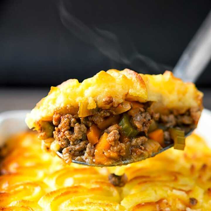 Square image of a serving spoon full of shepherds pie taken form a pie dish