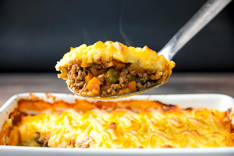 Landscape image of a serving spoon full of shepherds pie taken form a pie dish