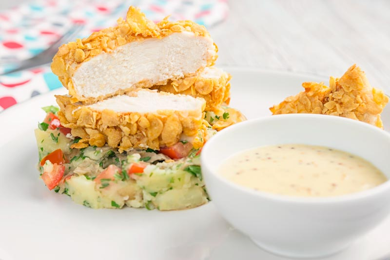 Landscape image of a sliced cornflake chicken breast served on crushed parsley potatoes and a mustard sauce