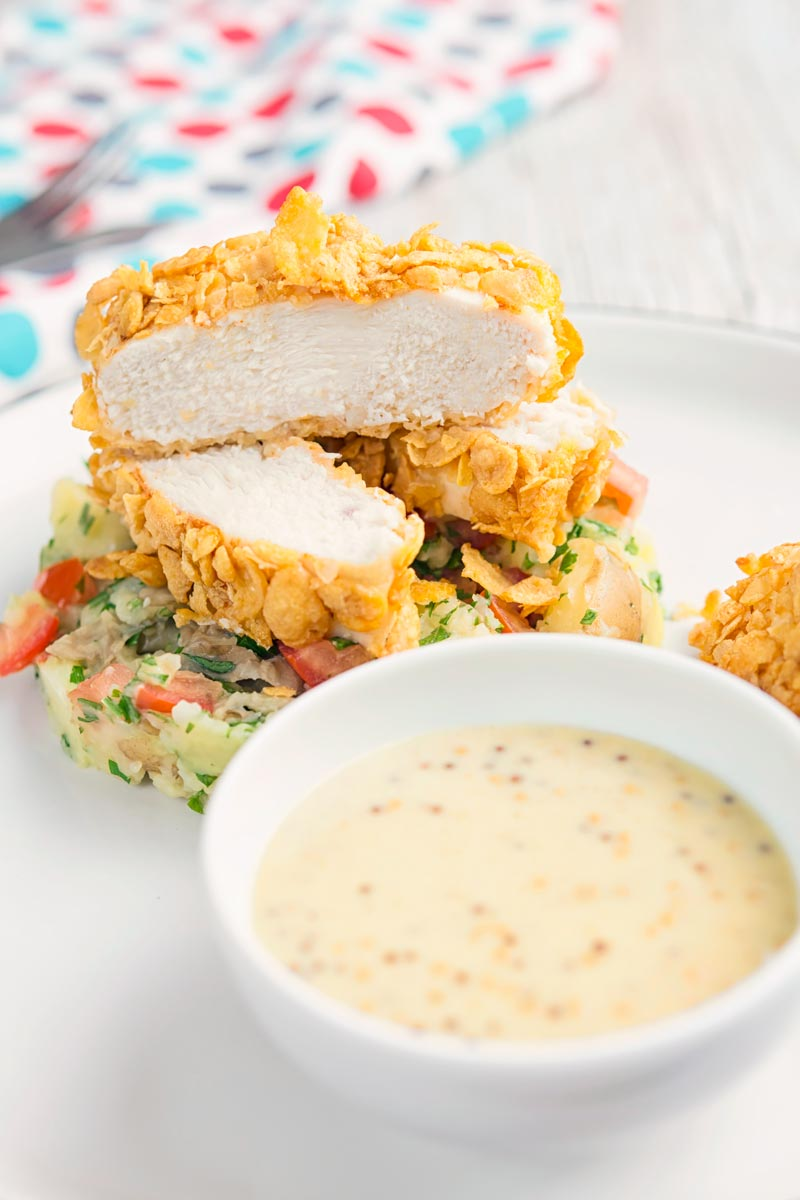Portrait image of a sliced cornflake chicken breast served on crushed parsley potatoes and a mustard sauce