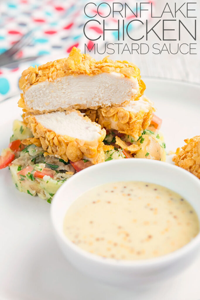 Portrait image of a sliced cornflake chicken breast served on crushed parsley potatoes and a mustard sauce with text overlay