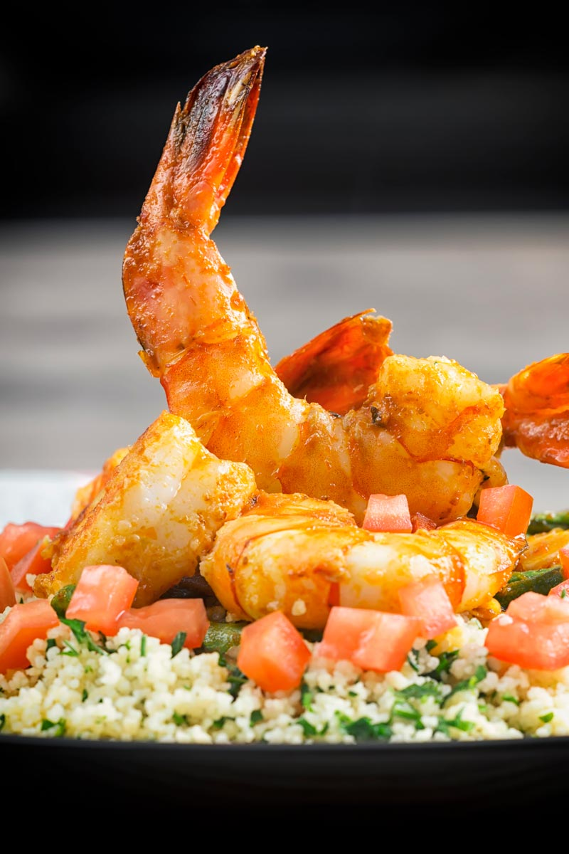 Portrait image of harissa garlic prawns served on a bed of buttered couscous