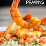 Portrait image of harissa garlic prawns served on a bed of buttered couscous with text overlay