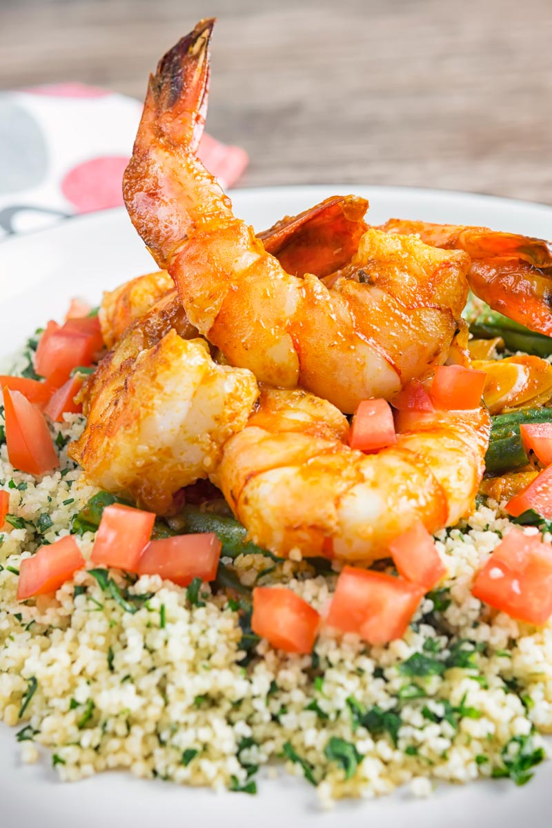 Portrait close up image of harissa garlic prawns served on a bed of buttered couscous served on a white plate