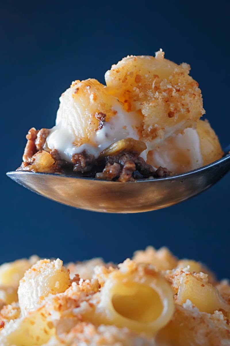 Portrait close up image of a spoon taking a portion of mac and cheese with beef from a blue bowl