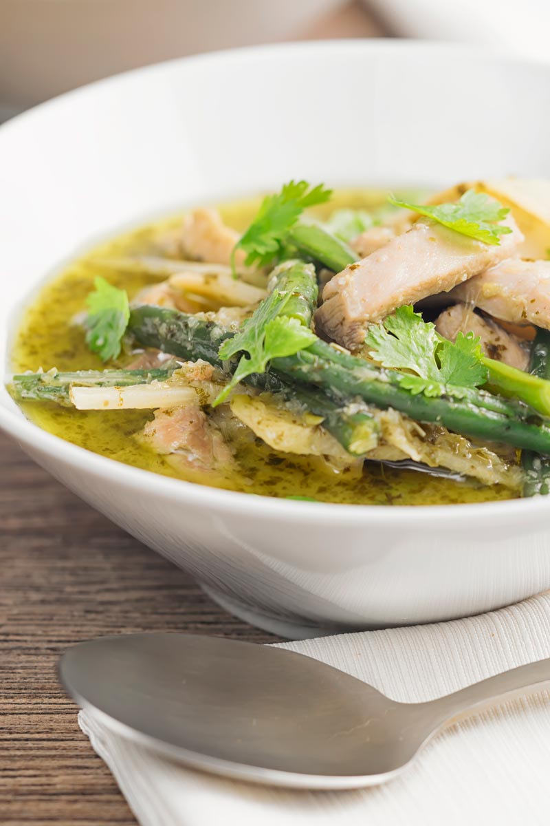 Portrait image of a Thai Green Chicken Curry featuring green beans and bamboo shoots served in a white bowl