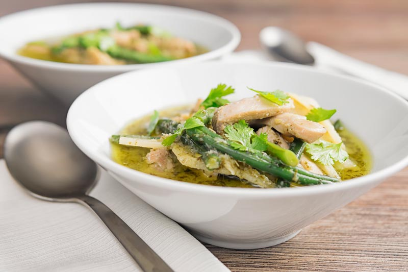 Landscape image of Thai Green Chicken Curry featuring green beans and bamboo shoots served in two white bowls