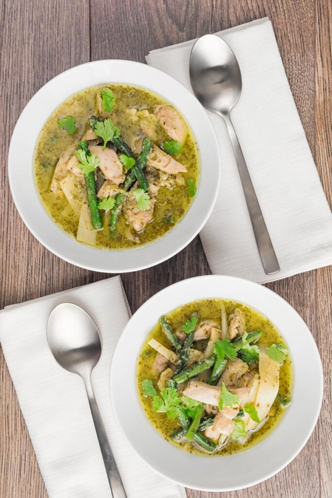 Portrait overhead image of Thai Green Chicken Curry featuring green beans and bamboo shoots served in two white bowls