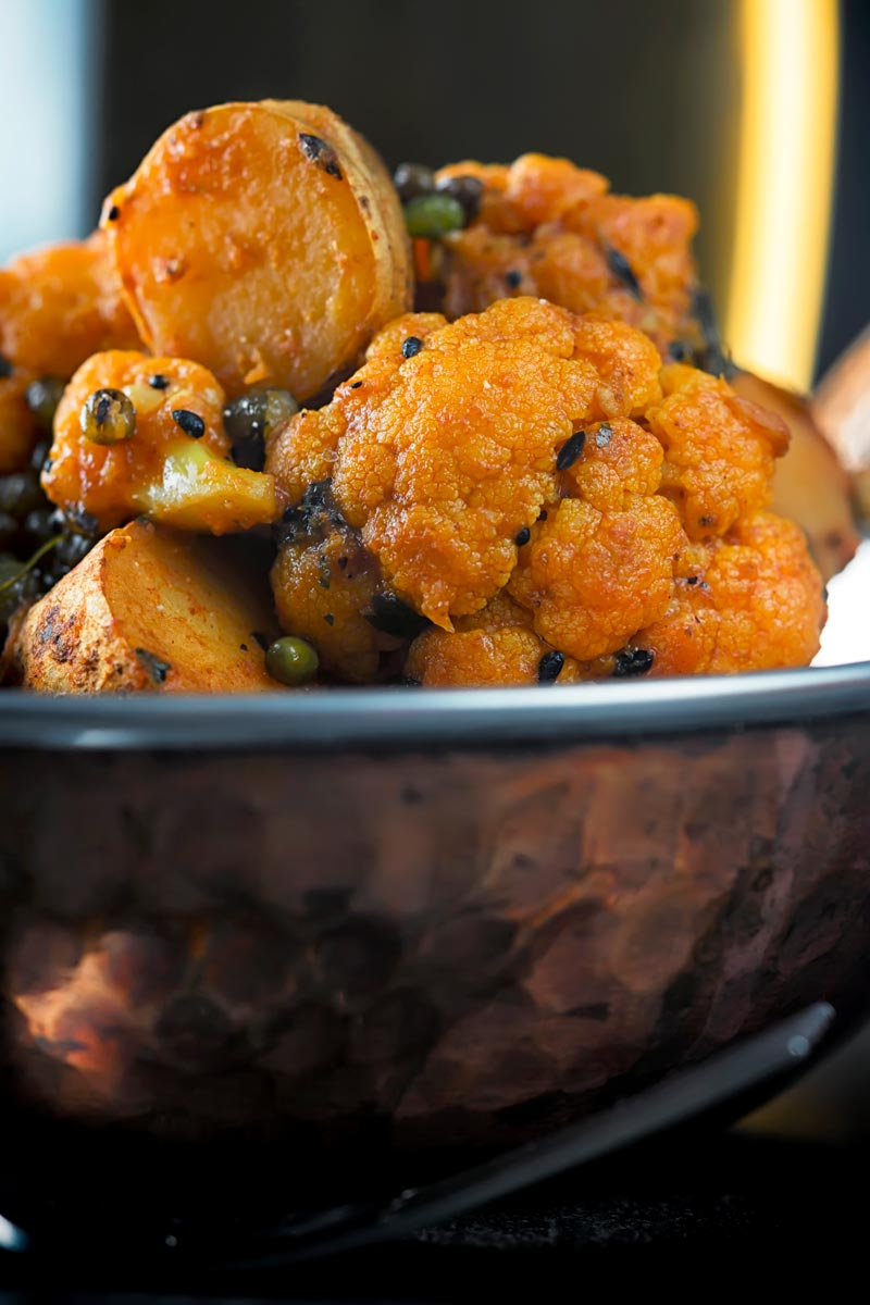 Portrait close up image of an aloo gobi Indian curry in a copper coloured curry bowl