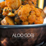 Portrait image of an aloo Gobi dry Indian curry in a copper coated curry bowl against a dark background with text overlay
