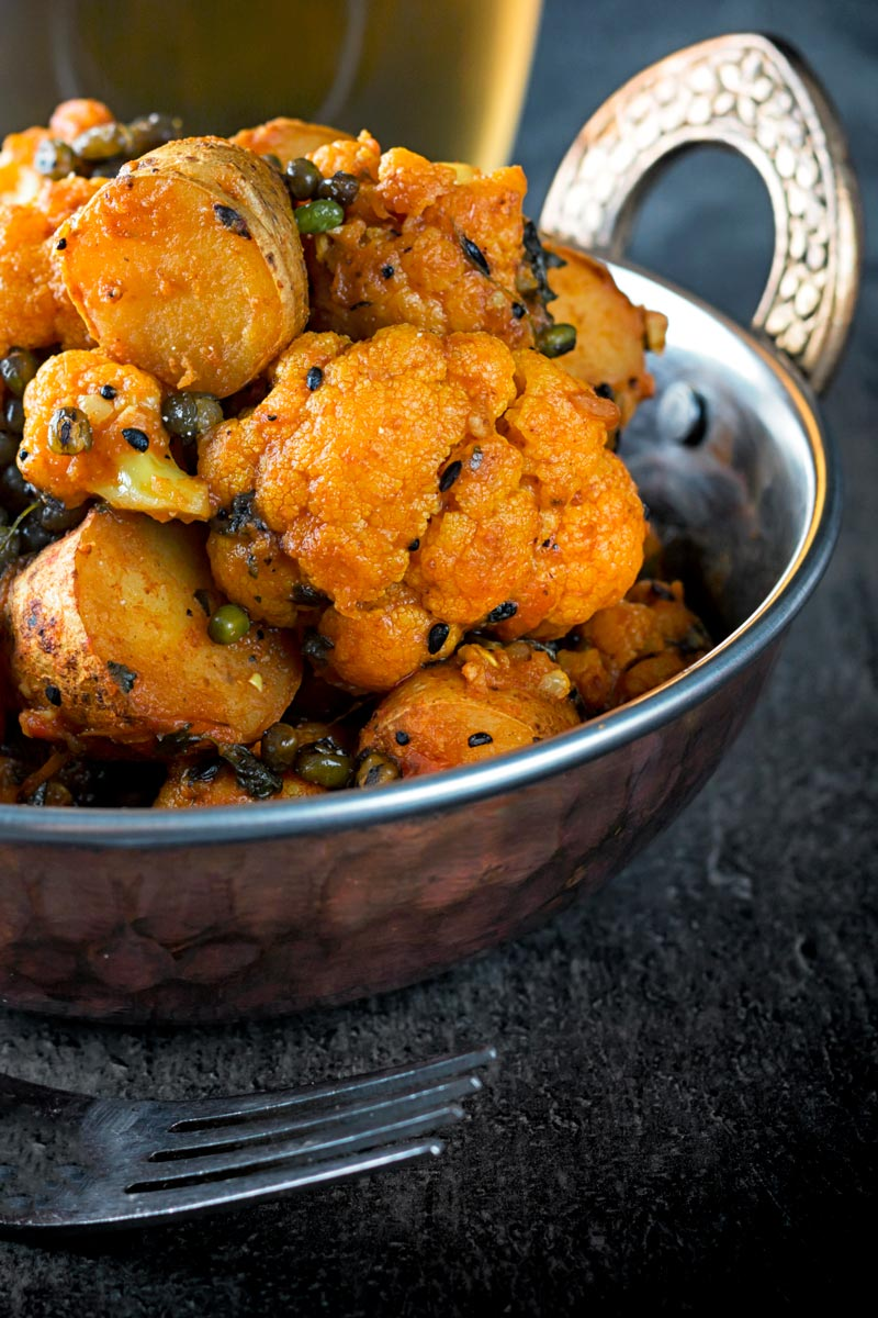 Portrait image of an aloo gobi Indian curry in a copper coloured curry bowl