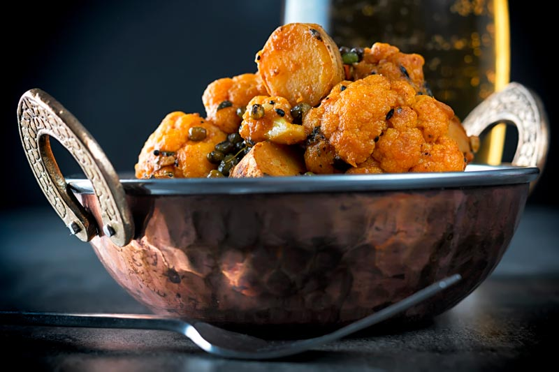 Landscape image of an aloo Gobi dry Indian curry in a copper coated curry bowl against a dark background