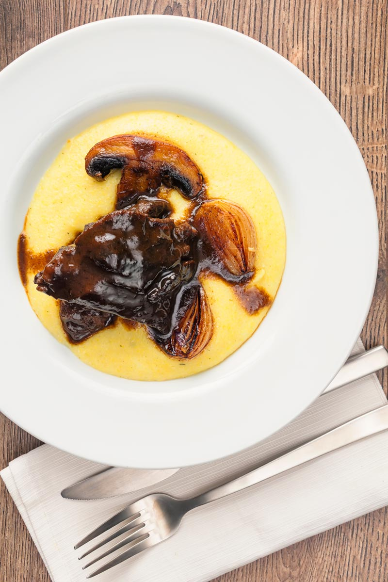 Portrait overhead image of beer braise beef cheeks with a rich glaze served with seared shallots and mushrooms on polenta