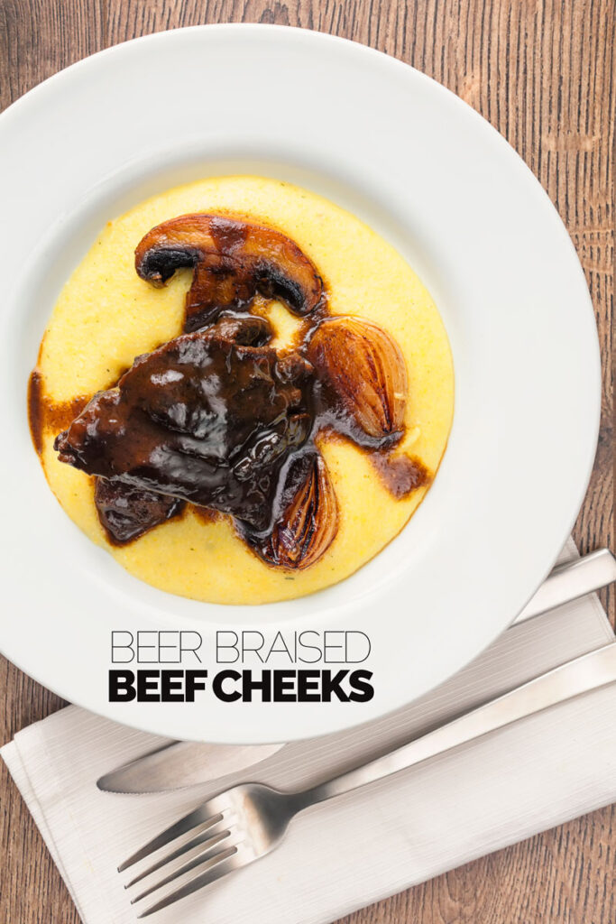 Portrait overhead image of beer braise beef cheeks with a rich glaze served with seared shallots and mushrooms on polenta with text overlay
