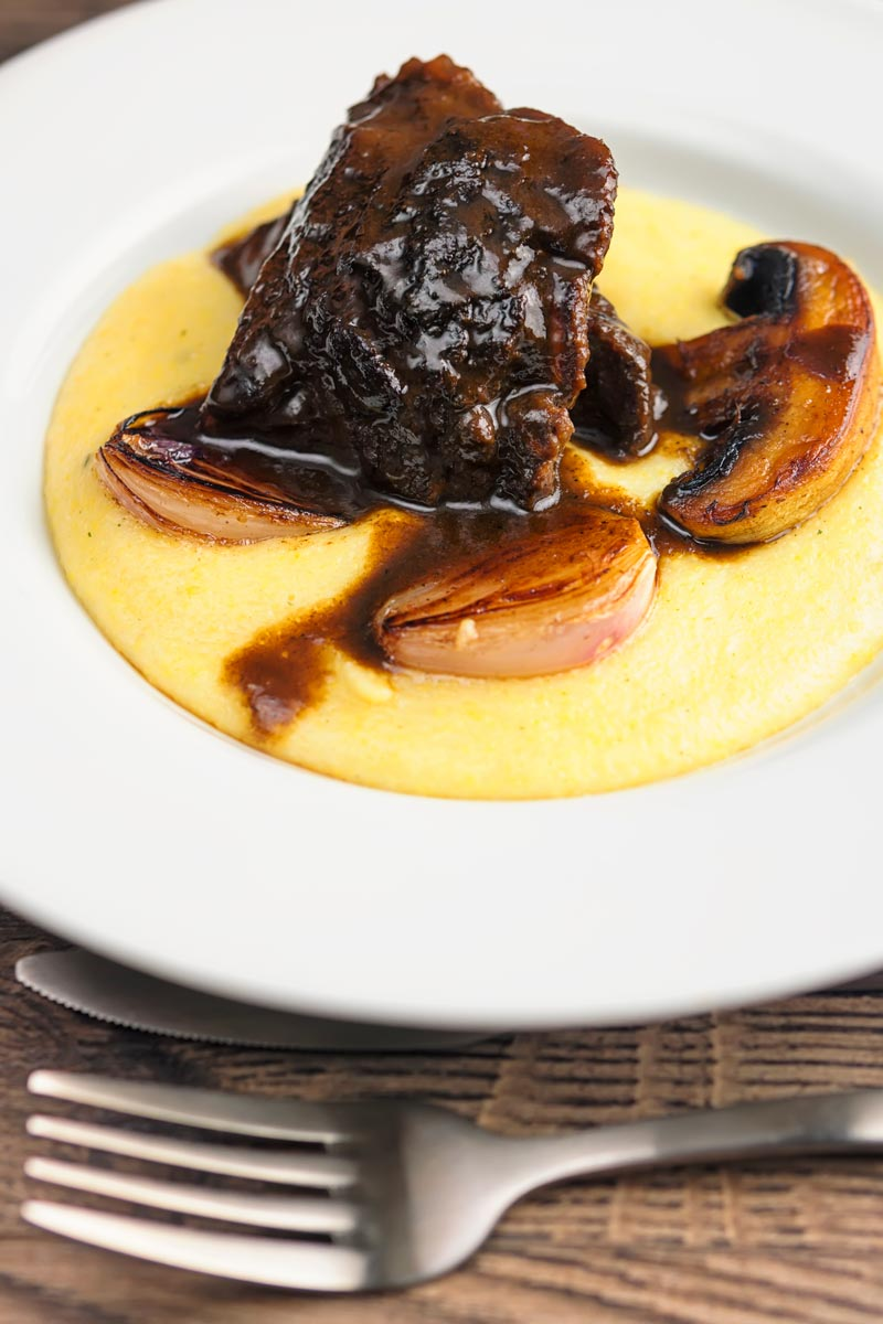 Portrait image of beer braised beef cheeks with a rich glaze served with seared shallots and mushrooms on polenta