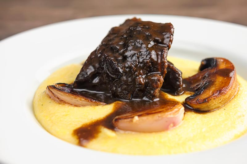 Landscape image of beer braised beef cheeks with a rich glaze served with seared shallots and mushrooms on polenta