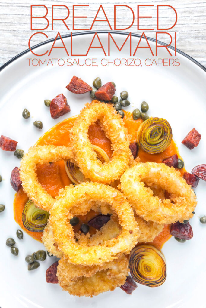 Portrait overhead image of breaded calamari rings served on tomato sauce with fried chorizo and capers served on a white plate with text overlay