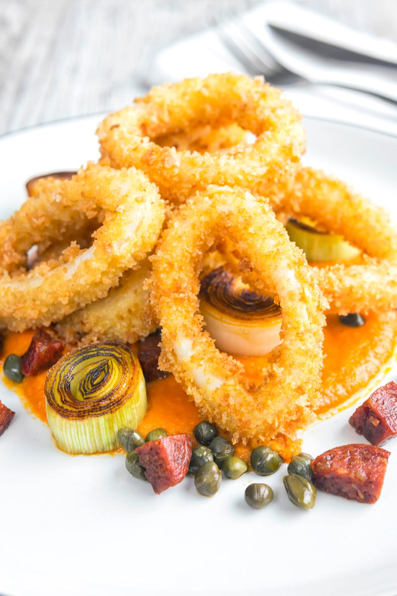 Portrait image of breaded calamari rings served on tomato sauce with fried chorizo and capers served on a white plate