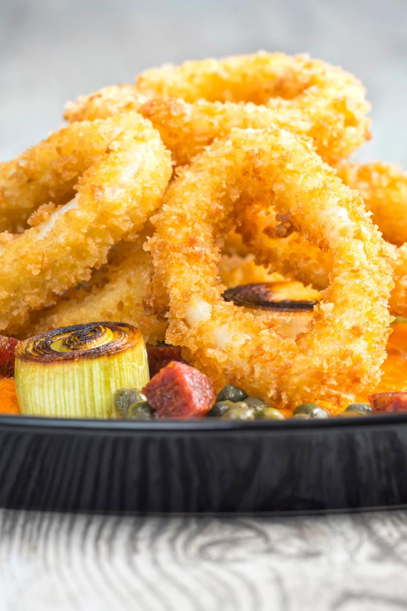 Portrait close up image of breaded squid rings served with fried chorizo, leeks and capers