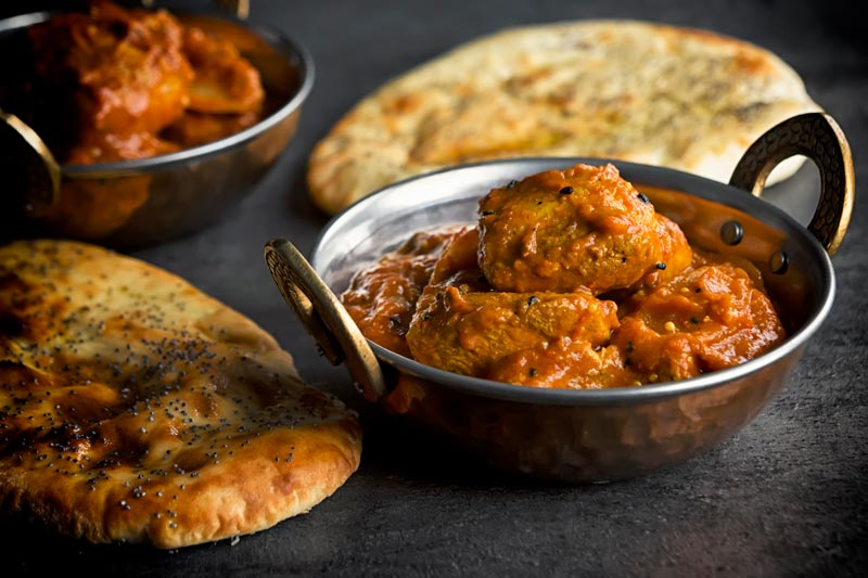 Landscape image of two Indian curry bowls filled with a chicken jalfrezi curry served with naan breads against a dark backdrop