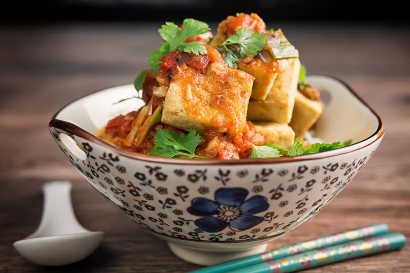 Landscape image of fried tofu cubes with a picy tomato sauce served in an Asian style bowl