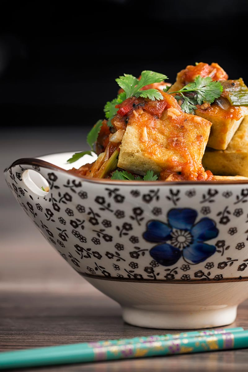 Portrait profile image of fried tofu cubes with a picy tomato sauce served in an Asian style bowl