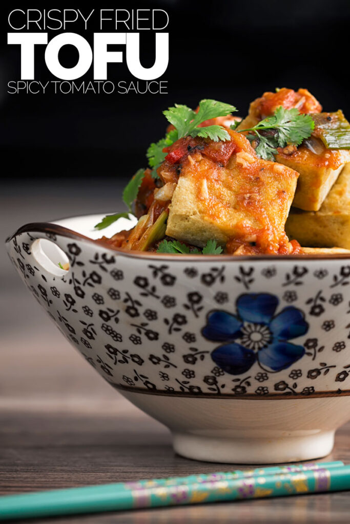 Portrait profile image of fried tofu cubes with a picy tomato sauce served in an Asian style bowl with text overlay