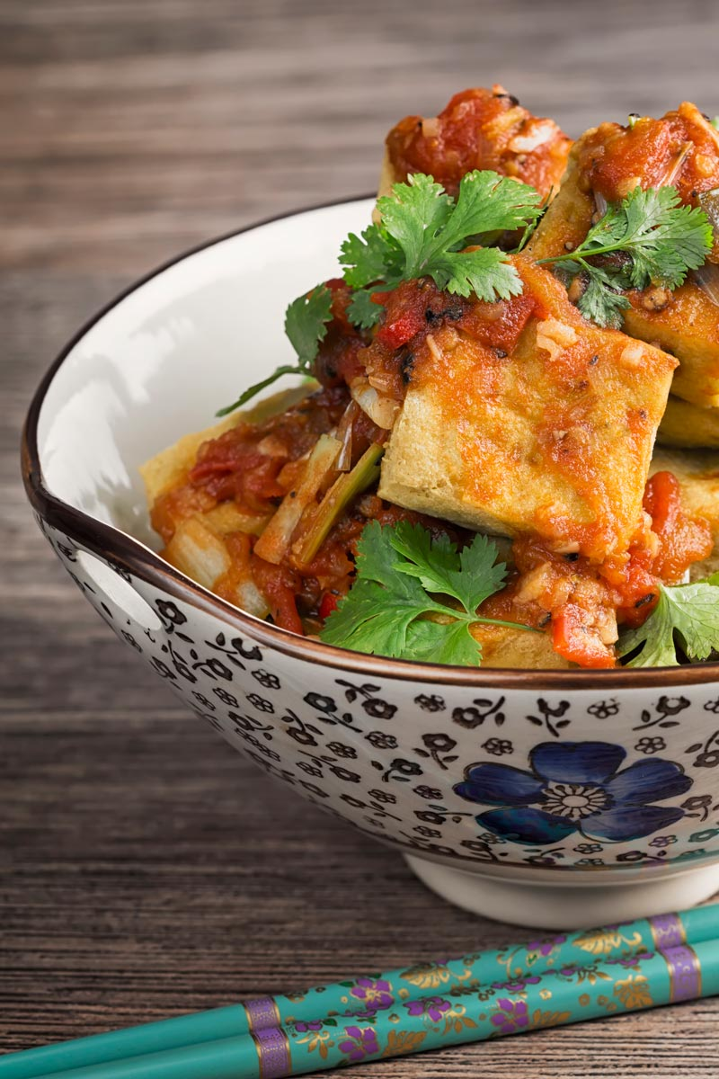 Portrait image of fried tofu cubes with a spicy tomato sauce served in an Asian style bowl
