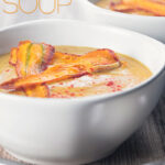 Portrait close up image of a creamy curried parsnip soup served in two bowls with fried carrot slices and paprika sprinkles with text overlay