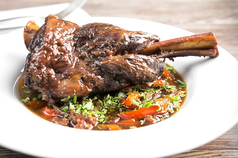 Landscape image of a Slow Cooker Lamb Shank served on a bed of braising liquid and red peppers served in a shallow white bowl