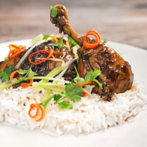Square image of garlic and ginger chicken legs served on a bed of white rice with julienned chilli and spring onions