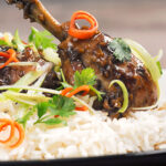Portrait close up image of garlic and ginger chicken drumstick served on a bed of white rice with jullienned chilli and spring onions with text overlay
