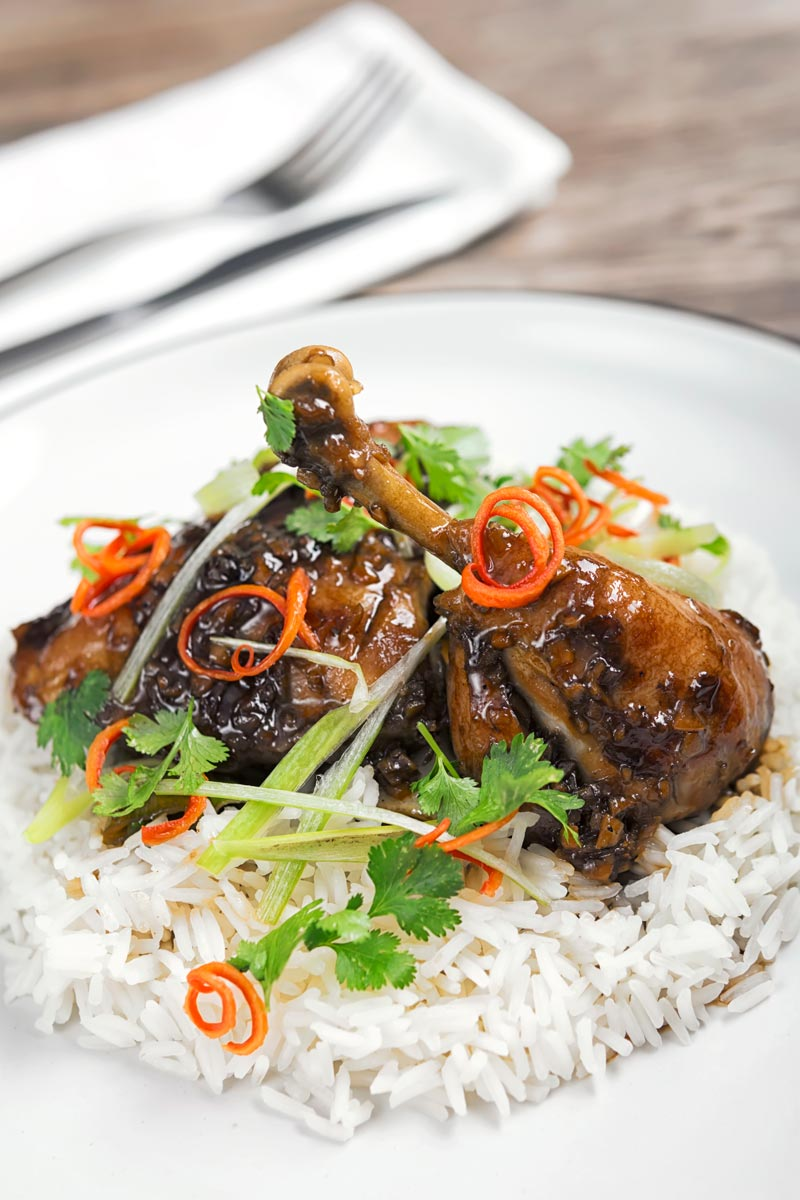 Portrait image of garlic and ginger chicken legs served on a bed of white rice with jullienned chilli and spring onions
