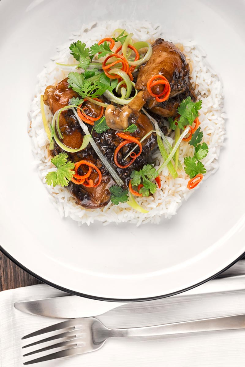 Portrait overhead image of garlic and ginger chicken legs served on a bed of white rice with julliened chilli and spring onions