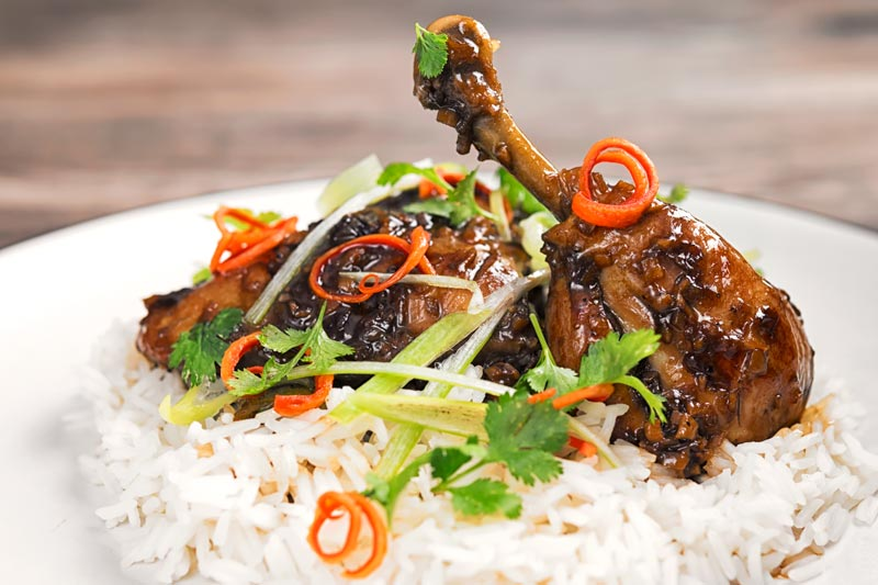 Landscape image of garlic and ginger chicken legs served on a bed of white rice with julienned chilli and spring onions